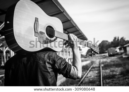 Guy with guitar on the railway road.Black and white photo