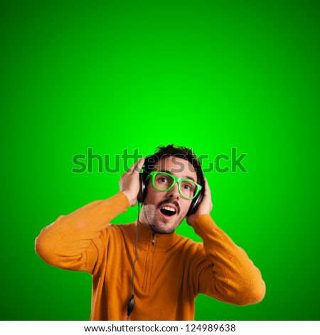 guy with headphones listening to music on green background
