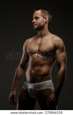 Guy with naked torso posing on grey background - stock photo