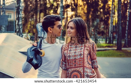 Guy with skateboard and attractive young female in a park. - stock photo