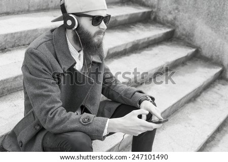 Guy with smartphone and headset listening to music - black and white photograph. - stock photo