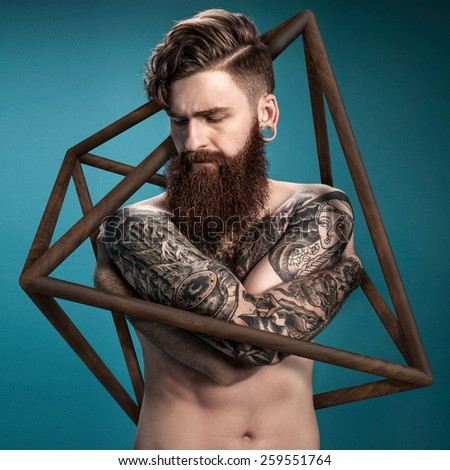Guy with tattoo in wooden case - stock photo