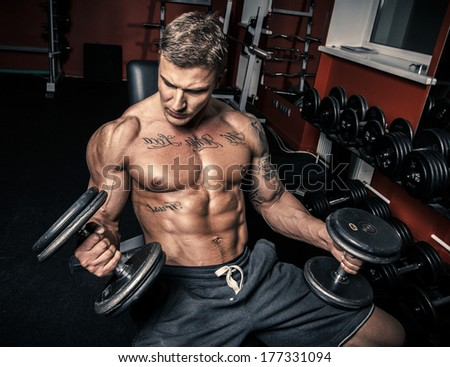 Guy with tattoos holding two dumbbells - stock photo