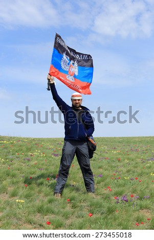 Guy with the flag DPR in the tulip field, Rostov region, Russia. - stock photo