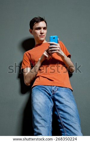 guy with the phone dials sms standing against the wall - stock photo