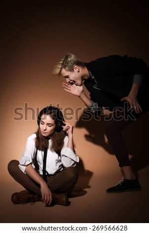 guy yells at her, �  She ignores it, listening to music - stock photo