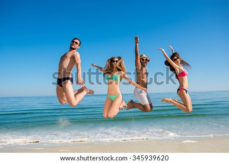 Guys and girls at the resort. Weekend at sea. Cheerful young people jumping on the beach.  Rest on the ocean. Company of friends having fun on the background of the sea. - stock photo