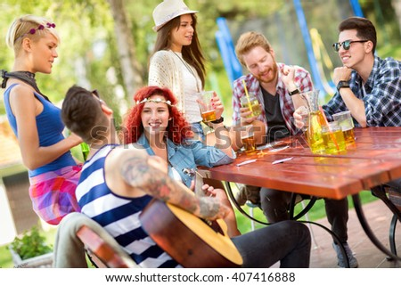 Guys and lassies spend sunny day in open in good mood with drinks and good guitar music - stock photo