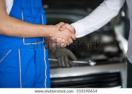 guys handshake  in auto repair service  - stock photo
