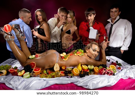 Guys having fun with women decorated  by fruits - stock photo