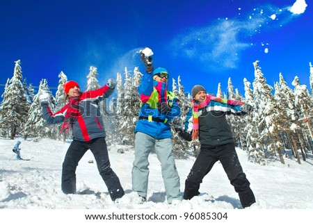 Guys having snowball fight in snow in winter background - stock photo