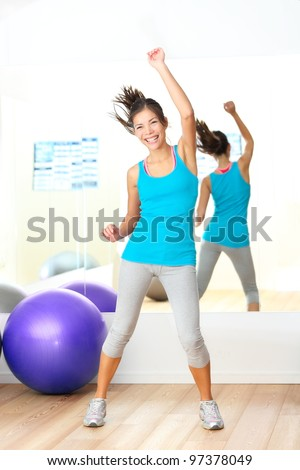 Gym aerobics fitness dance instructor. Woman dancing happy in fitness center. Young beautiful mixed race Caucasian / Chinese Asian female fitness model.