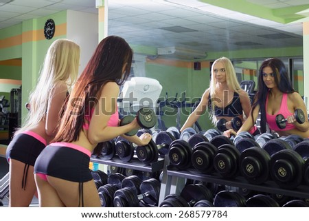 Gym. Athletes admire reflection in mirror - stock photo