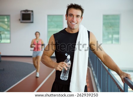 Gym: Athletic Man Stands By Rall To Rest - stock photo