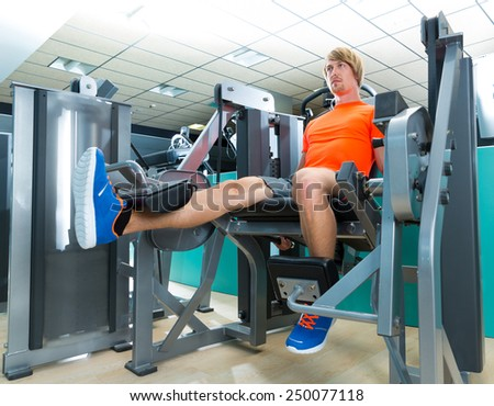Gym blond man leg extension cuadriceps exercise workout at indoor - stock photo