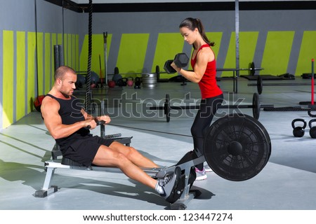 Gym couple with dumbbell weights and fitness power workout - stock photo