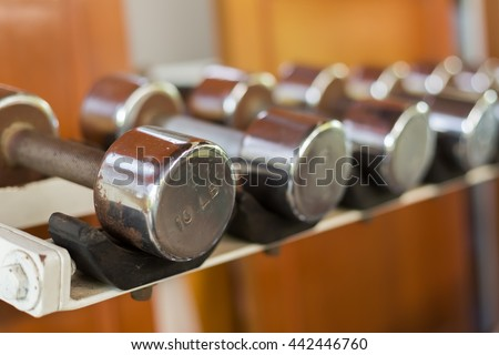 Gym equipment background with close up selective focus to a dumbbell