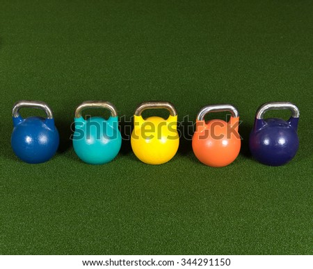 Gym Equipment for Bootcamp Type Classes.  Variable Weight Kettle Bells on Green Turf - stock photo