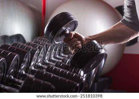 Gym equipment, hand holding dumbbell. Sport background. - stock photo