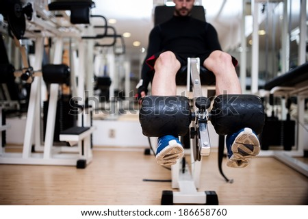 Gym fitness center with young man working out the legs - stock photo