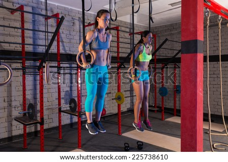 Gym girls muscle ups rings workout at gym - stock photo