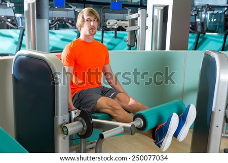 Gym leg extension exercise workout man indoor - stock photo
