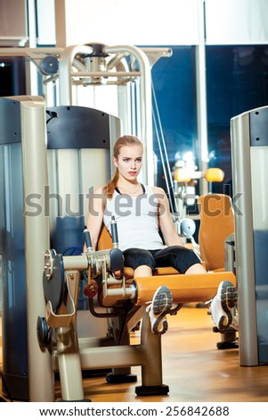 Gym leg extension exercise workout woman indoor. - stock photo