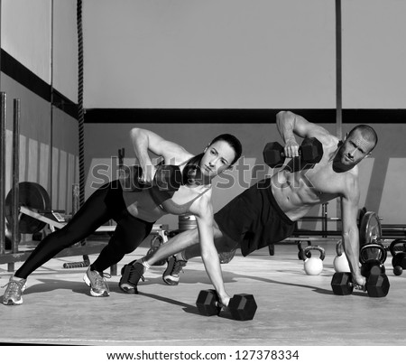 Gym man and woman push-up strength pushup with dumbbell in a workout - stock photo