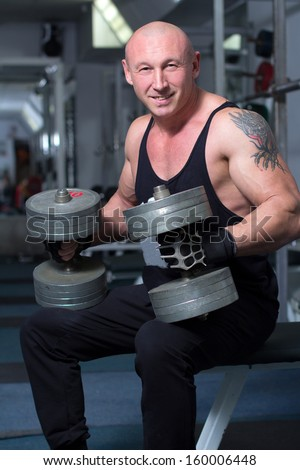 Gym Man. Man with weight training equipment on sport gym club - stock photo