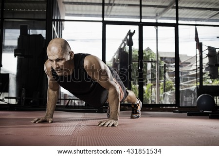 Gym man push-up strength pushup exercise with dumbbell in a crossfit workout - stock photo