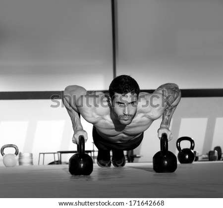 Gym man push-up strength pushup exercise with Kettlebell in a crossfit workout - stock photo
