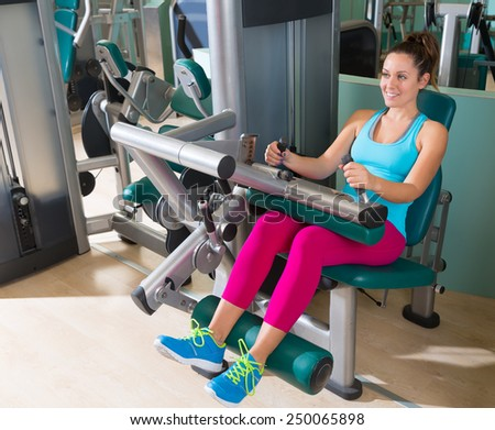 Gym seated leg curl machine exercise woman at indoor - stock photo