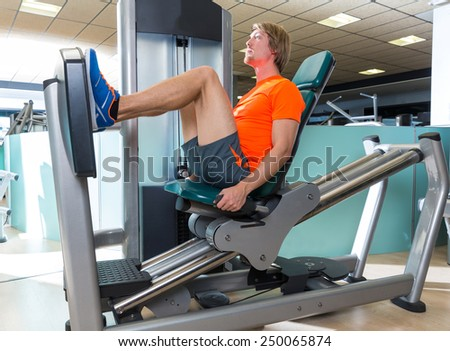 Gym seated leg press machine blond man workout at indoor - stock photo