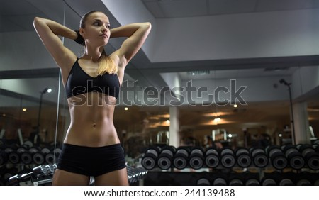 Gym.Sporty girl posing here belly press - stock photo