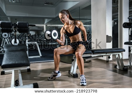 Gym.Sporty girl posing with dumbbells - stock photo