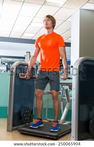 Gym squat machine exercise workout blond man at indoor - stock photo