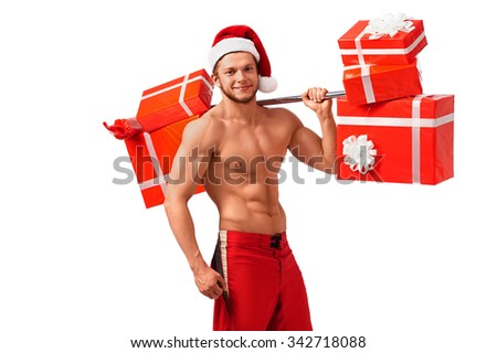 Gym tonight. Muscular Santa Claus holding a barbell with presents on his shoulder - stock photo