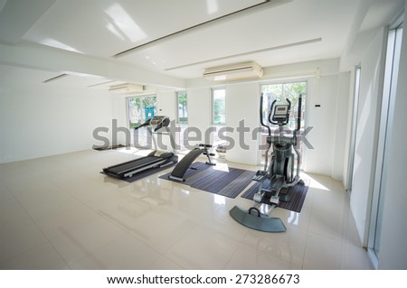 Gym with power dumbell lifting, stationary bicycle standing and elliptical cross trainers equipment