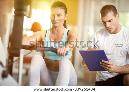 Gym woman and her trainer doing exercise at the gym. - stock photo