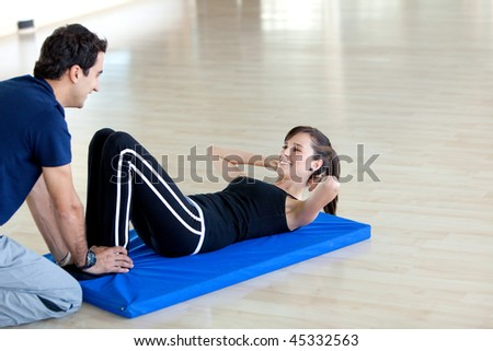 Gym woman doing exercises for her abs with her trainer - stock photo