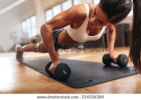 Gym woman doing push-up exercise with dumbbell. Strong female doing crossfit workout. - stock photo