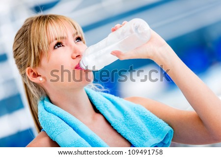 Gym woman drinking water from a bottle - stock photo
