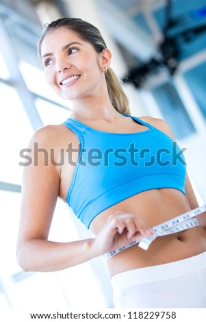 Gym woman measuring her waist and smiling - stock photo