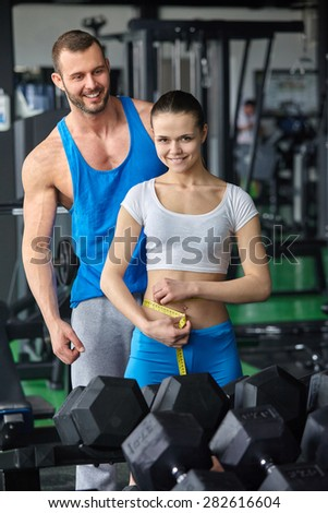 gym woman personal trainer man with weight training equipment in modern gym - stock photo