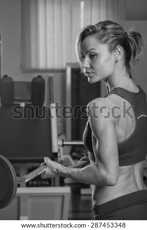 Gym woman push-up strength pushup exercise with dumbbell in a fitness workout. Athletic young woman doing exercises.