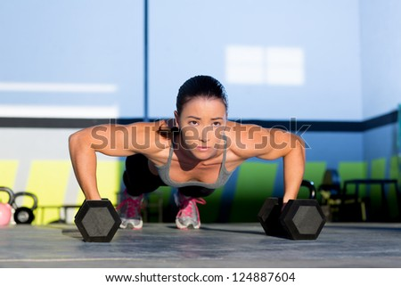 Gym woman push-up strength pushup exercise with dumbbell in a workout - stock photo