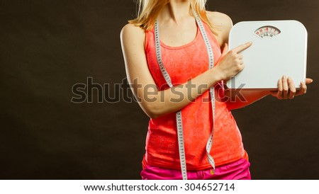 Gym woman with measure tape holding weight scale studio shot black background - stock photo