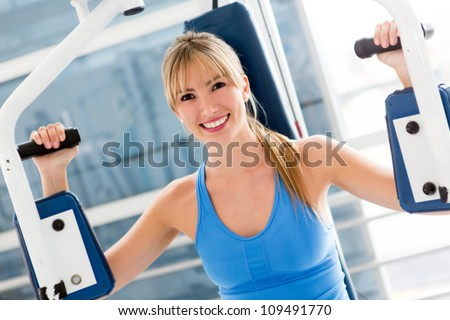 Gym woman working out on a machine - stock photo