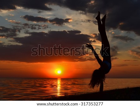 Gymnast exercising near the sea.