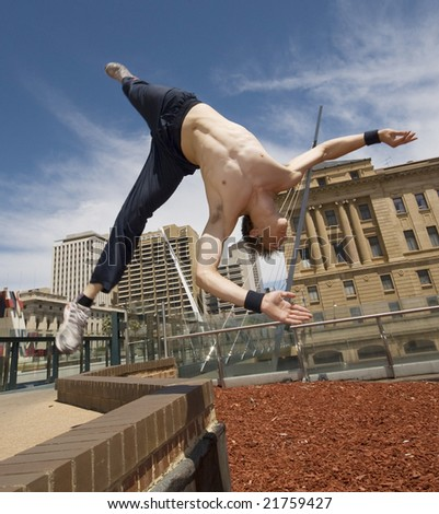 Gymnast flips off block infront of city buildings
